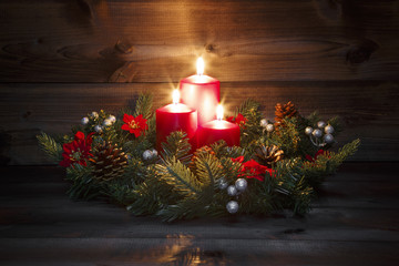 Third Advent - Decorated Advent wreath with three red burning candles on a wooden background with festive atmosphere