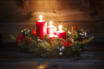 Fourth Advent - Decorated Advent wreath with four red burning candles on a wooden background with...