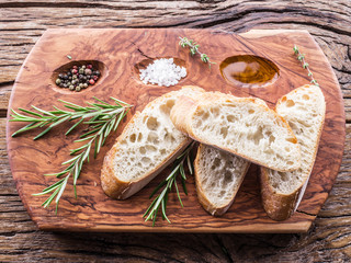Slices of ciabatta with rosemary herb on the serving wooden tray