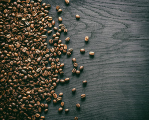 Roasted coffee beans on the old wooden background. Top view.