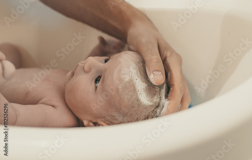 Portrait of a baby is being bathed by his father using tub at home ...