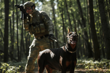 Image of airsoft player with dog and submachine gun