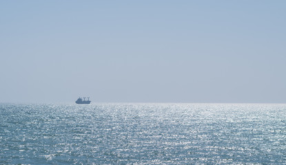 Calm glittering sea and cloudless sky.