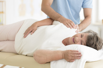 Masseur massaging senior woman's shoulders