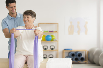 Smiling physiotherapist helping older woman
