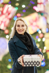 Portrait of blonde in coat with gift box on background of Christmas tree