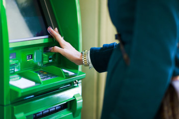 Photo of woman with clock on hand at green cash machine