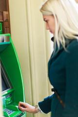 Photo of blonde in coat at green cash machine