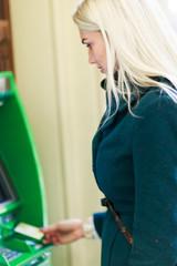 Image of blonde in coat at green cash machine