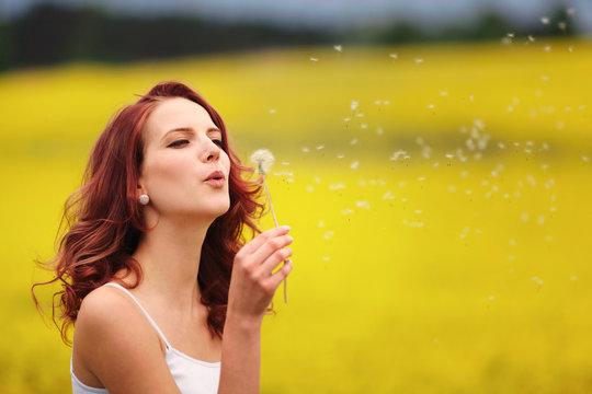 beautiful woman blowing dandelion in the field