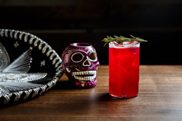 A horizontal image of a red cocktail with ice cubes in a highball glass, decorated with rosemary. Sombrero and a mexican colourful skull near by.
