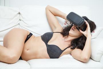 bella donna nuda sul divano si aggiusta gli occhiali per realtà virtuale