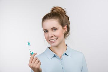 Junge Frau hält eine Zahnbürste und schaut freundlich zum Betrachter