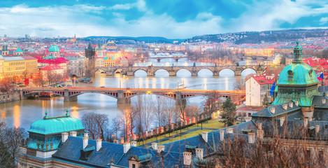 Prague, Czech Republic. Beautiful view from above over bridges and river Vltava. Winter scenery. Twilight scene. Panoramic aspect ratio photo. Artistic post processing.