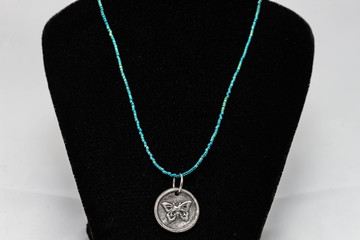multi shade blue beaded necklace with a silver pendant