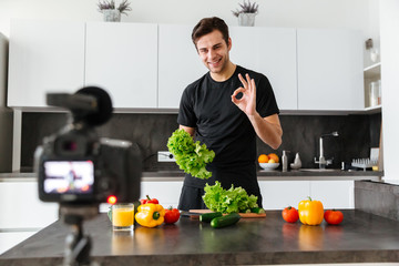 Smiling young man filming his video blog episode