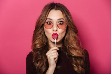 Funny lady wearing glasses eating candy.