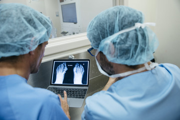 Doctors exploring X-ray on laptop