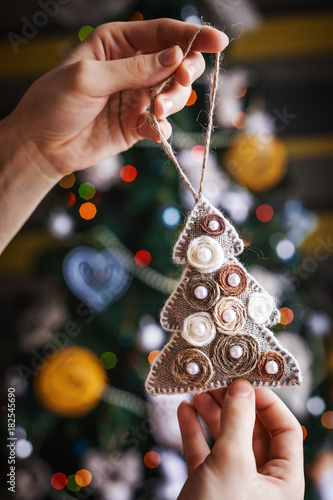 little beauty new year tree in hands background and christmas decorations with toys sparkling