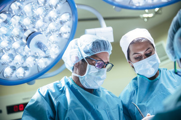 Specialists working with patient in surgery room