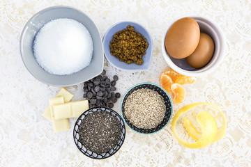 mantel de encaje con ingredientes para hacer dulces como azucar moreno y blanco cascara de limón y de naranja, gajos de mandarina,chocolate negro y  blanco, semillas de amapola blancas y negras