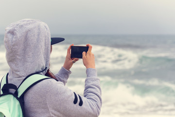 Woman tourist taking pictures of sea with mobile phone, woman using mobile phone at sea