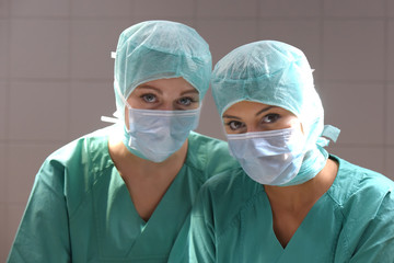 Two young women pose in a low lit operation theater.  Fully dressed as theater nurses with face masks  and green sterile medical work clothing.