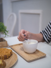 Woman hand holding the spoon to stir hot milk