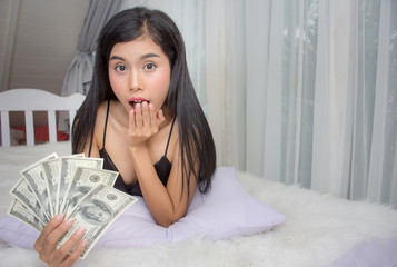 Young Asian girl dressed sexy model holding money dollar bills and looking at camera feel surprised lie down on the bed