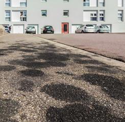 Umweltverschmutzung, Gehweg mit Motorölflecken – Pollution, walkway with stains from engine oil