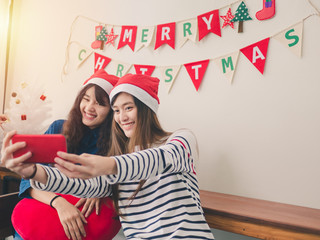 Two asia women smiling take photos in christmas party, Have Christmas Tree Ornaments.