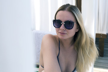attractive blonde girl with sunglasses in the beach bungalow near the sea