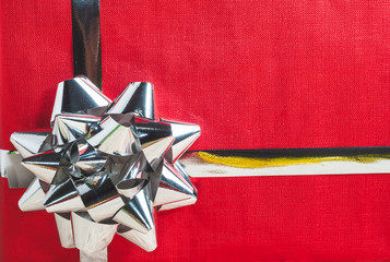 Close up to red paper gift box with silver ribbon and bow