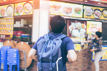 Young man traveler is visiting at Mongkok in Hong Kong for find some restaurant for eat noodles