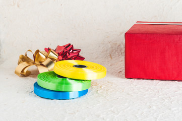 Red present box behind heap of Colorful ribbon stripes on textured paper background