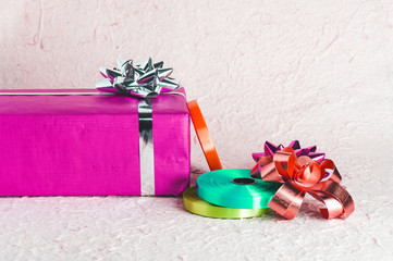 Pink gift present box with heap of Decoration supplies like ribbon and bow on textured paper surface for your Christmas design