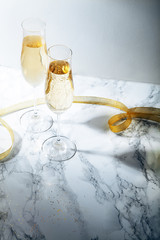Two flute glasses with champagne on marble background. Direct light with heavy shadows. Vertical composition