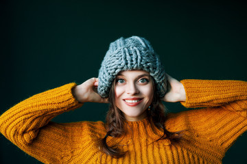 Close up portrait of young beautiful happy smiling girl wearing stylish grey big loop knitted beanie hat and yellow sweater. Model looking at camera, posing on dark green background.