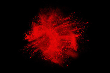 Abstract explosion of red dust  on  black background. Abstract red powder splatter on dark  background. Freeze motion of red powder splash.