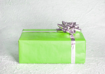 Green gift box with silver ribbon and bow on textured paper background