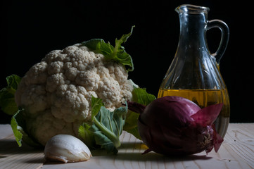 Low key still life with cauliflower, onion, garlic and olive oil on a wooden table