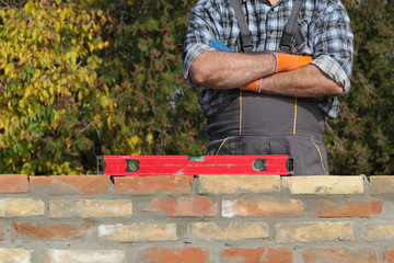 Worker control brick wall, examining using level tool, real people, no retouch