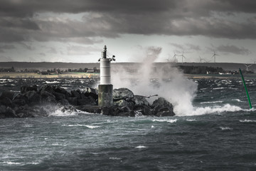 Waves splashing against rocks and a small lighthouse
