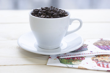 Christmas still life with white coffee cup with saucer on a wooden table. The cup filled with coffee beans. Light background. Close up