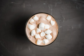Hot chocolate with marshmallow on the wooden background. Shallow depth of field. Toned image.