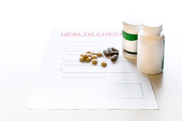 A blank health check form with medicine, vitamins and pills. Plastic medicine containers with label and copy space.