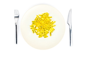 Soft yellow capsules with healthy omega 3 fish liver oil on a dinner plate with knife and fork. Seen from above.