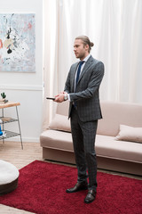 Businessman standing and holding remote controller at home