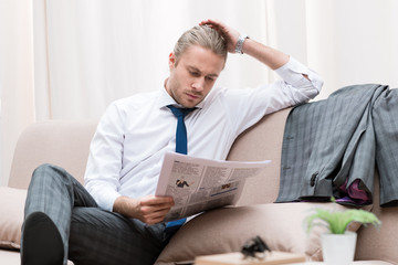 concentrated businessman reading newspaper on sofa at home