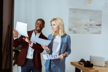 smiling interracial photographers choosing photos while standing at window in office